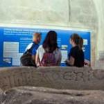 (Español) 3 personas de espalda leyendo cartel de museo